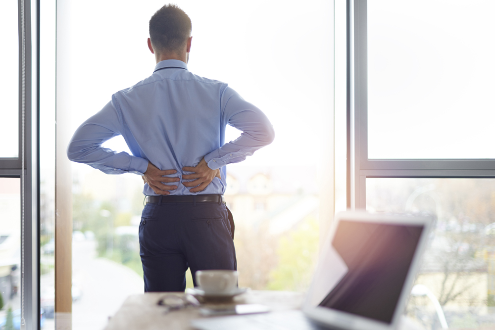 man suffering from lower back pain in his office
