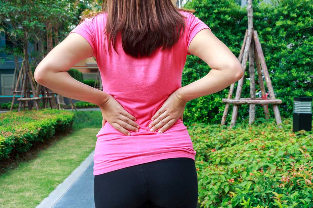 Woman with back pain needs chiropractic care.
