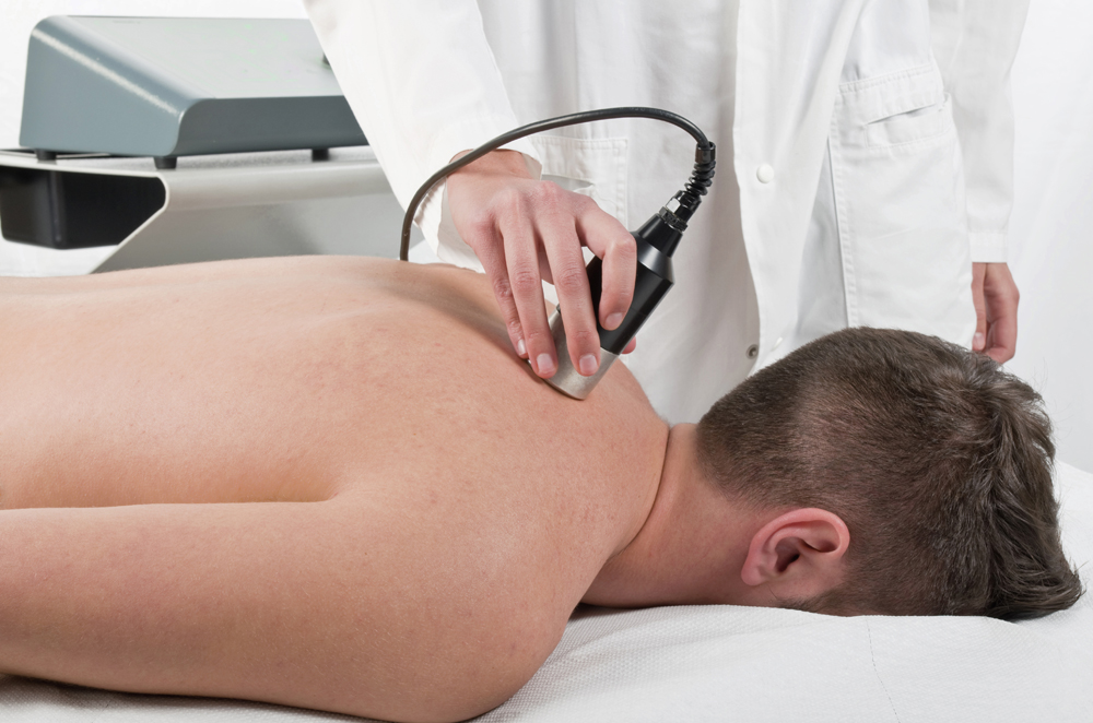 man receiving laser treatment on his upper back
